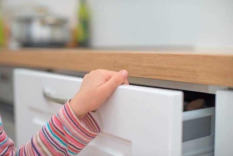 Eine Kindersicherung für Schränke sorgt für Sicherheit